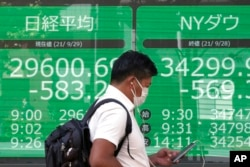 A man wearing a protective mask walks in front of an electronic stock board showing Japan's Nikkei 225 and New York Dow indexes at a securities firm, Sept. 29, 2021, in Tokyo.