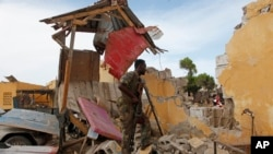 A Somali soldier stands amid ruins in Mogadishu, May, 9, 2016, after a suicide car bomber linked to al-Shabab struck traffic police headquarters. Somali and U.S. special forces led a joint raid Tuesday on a terrorist base.