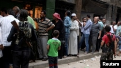 FILE - Rebel fighters stand guard as people queue for bread in the rebel held al-Shaar neighborhood of Aleppo, Syria, July 14, 2016.