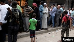 Rebel fighters stand guard as people queue for bread in the rebel held al-Shaar neighborhood of Aleppo, Syria July 14, 2016.