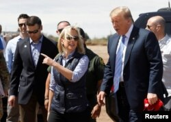 FILE - Homeland Security Secretary Kirstjen Nielsen, center, and commissioner for Customs and Border Patrol Kevin McAleenan, left, walk with U.S. President Donald Trump during a visit to a section of the border wall in Calexico California, April 5, 2019.