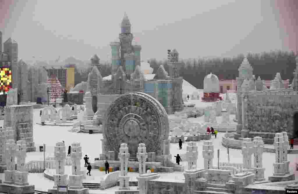 Khách đến xem các tác phẩm khắc bằng băng đá trước ngày Lễ hội Băng Tuyết lần thứ 31 ở thành phố Cáp Nhĩ Tân, tỉnh Hăc Long Giang, Trung Quốc. Lễ hội mùa đông này sẽ chính thức khai mạc vào ngày 5 tháng 1, 2015.