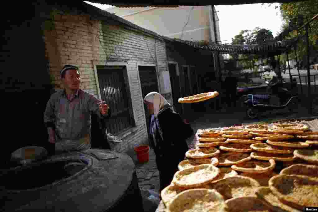 اویغورها، اقلیت عمدتاً مسلمان ساکن شمال غرب چین، سنت های قدیمی خود را حفظ کرده اند. مرد اویغور در حال پخت نان در بازار محلی اورومچی - استان سین کیانگ، اکتبر ۲۰۱۳