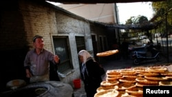 吐鲁番当地市场一位烤馕的维吾尔族男士。