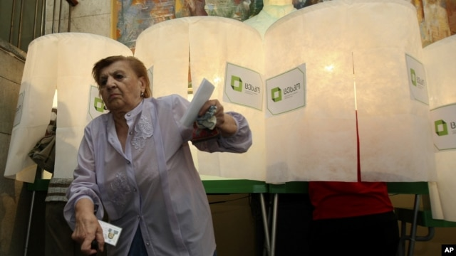 A woman leaves a voting booth at a polling station in Tbilisi, Georgia, October 1, 2012.