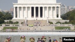 FILE - Soldiers dressed in WWII uniforms place wreaths in front of the Freedom Wall, with the Lincoln Memorial in the background, at the World War II Memorial in Washington, May 8, 2015.