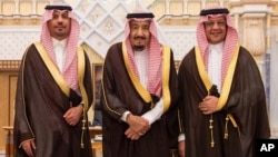 In this photo provided by the Saudi Press Agency, the new Economy and Planning Minister, Mohammad al-Tuwaijri, right and the new National Guard chief, Prince Khalid bin Ayyaf al-Muqrin, left, pose for a photo with King Salman during a swearing in ceremony, in Riyadh, Saudi Arabia, Nov. 6, 2017. The king has sworn in new officials to take over from a powerful prince and former minister believed to be detained in a large-scale sweep that has upended longstanding traditions.