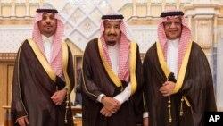 Dalam foto yang dirilis oleh Kantor Berita Arab Saudi ini, Menteri Perekonomian dan Perencanaan baru, Mohammad al-Tuwaijri (kanan) dan kepala Garda Nasional yang baru, Pangeran Khalid bin Ayyaf al-Muqrin (kiri) berpose bersama Raja Salman dalam upacara pengambilan sumpah jabatan di Riyadh, Arab Saudi, 6 November 2017. (Foto: dok/Saudi Press Agency, via AP).