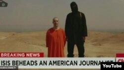 Người đàn ông mặc đồ đen cho biết người đàn ông quỳ gối là James Wright Foley và tố cáo chính phủ Mỹ cầm đầu cuộc xâm lăng Nhà nước Hồi giáo.