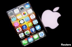 An Apple iPhone is pictured next to the logo of Apple in Bordeaux, southwestern France, Feb. 26, 2016.