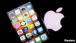 An Apple iPhone is pictured next to the logo of Apple.