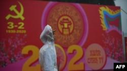Một cảnh sát làm nhiệm vụ bên cạnh áp phích kỷ niệm 90 năm ngày thành lập Đảng Cộng sản Việt Nam, ngày 3/2/2020.