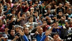 Protesters chant slogans against mass death penalties outside of Cairo University.