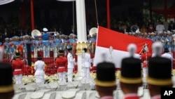 Para pembawa bendera mengibarkan bendera merah putih nasional Indonesia dalam upacara peringatan kemerdekaan di Istana Merdeka di Jakarta, Indonesia, Jumat, 17 Agustus 2018. (Foto: AP)