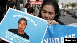Una mujer muestra el retrato de su hijo desaparecido en México víctima de la violencia.
