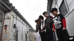 搬進臨時住所的日本地震幸存者星期一向地震死難者默哀