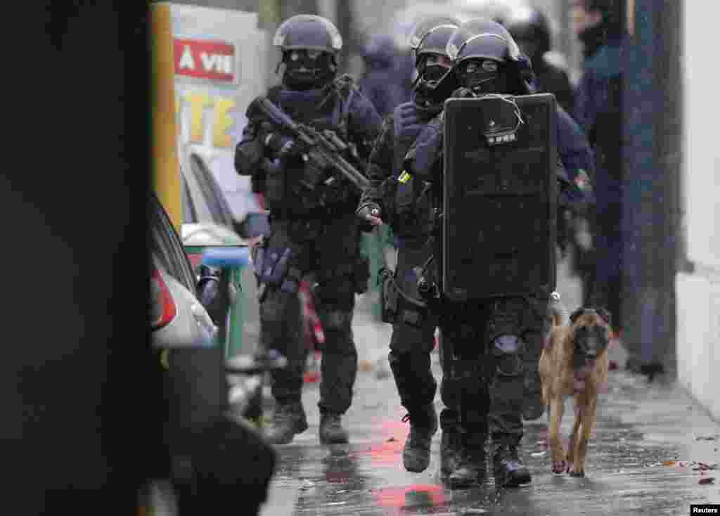Armed French intervention police walk with a sniffer dog at the scene of a shooting in the street of Montrouge, near Paris, Jan. 8, 2015.