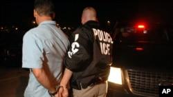 Un agente de la agencia de Inmigración y Control de Aduanas arresta a un hombre recogido en Brockton, Massachusetts.