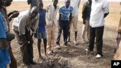 Civilians at the site of a bomb crater in Thaon village in Bentiu town, South Sudan, April 12, 2012.