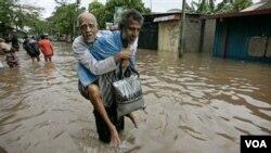 Seorang warga membantu seorang kakek untuk mengungsi dari banjir di Srilanka, Sabtu (15/1).