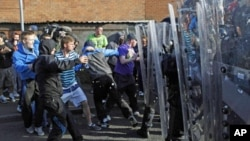 Youths attack police in Ardoyne in Belfast, Northern Ireland. Police firing plastic bullets and powerful water cannons forced Catholic militants away from a disputed Belfast road Tuesday as Northern Ireland's annual day of Protestant marches reached a fie