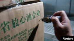 """2018年7月4日,在中國山東省曲阜市,在糧油工業和進出口公司的工廠,瓶裝大豆油的盒子上印著""""放心油企業""""""""原料產國:美國""""。"""
