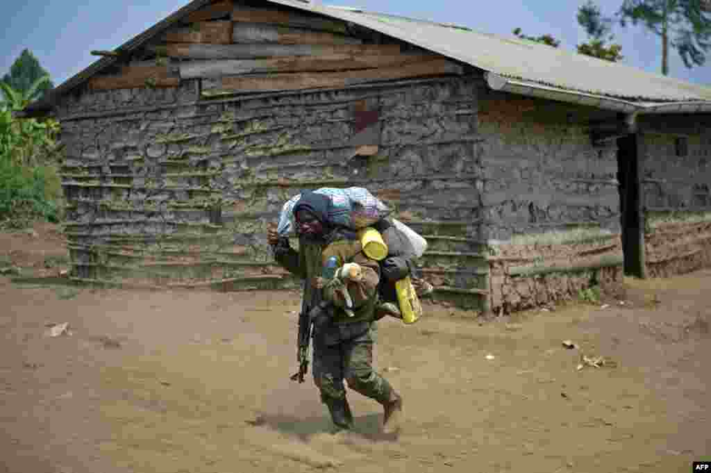 A Congolese army soldier, holding a dog, walks through the village of Rusayo, which was the scene of heavy clashes on July 15, about 13km from Goma in the eastern region of the Democratic Republic of the Congo. Combat continued between the national army and M23 rebels.