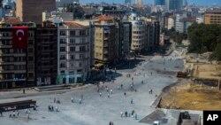 Abantu bariko baratambuka mu mabarabara ari hafi ya Park yitwa Gezi, iri hafi y'iikibanza Taksim Square, mu gisagara ca Istanbul, muriTurkey, kw'igenekerezo rya 17, umwaka w' 2013.