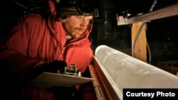Climate scientist studies ice core from Antarctica. (T. Bauska)