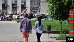 A young couple walks near a barricade outside the regional administration building in Ukraine's eastern city of Donetsk, occupied by pro-Russia insurgents, on May 14, 2014.