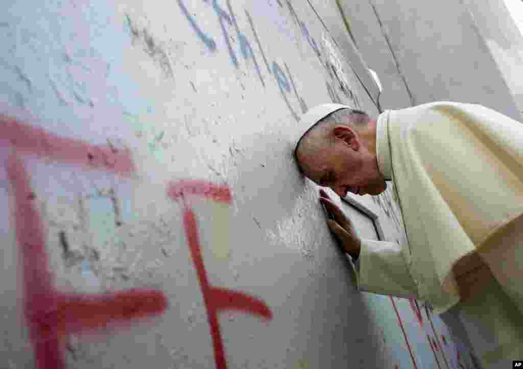 Pope Francis touches the wall that divides Israel from the West Bank, on his way to celebrate a mass in Manger Square next to the Church of the Nativity, believed by many to be the birthplace of Jesus Christ, in the West Bank town of Bethlehem.