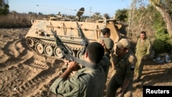 Israeli soldiers unload their weapons near the border with the Gaza Strip August 20, 2014.