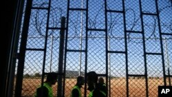 Guards walk past a razor wire fence securing a former prison in Drahonice, Czech Republic, Friday, Oct. 2, 2015. Anticipating a possible influx of migrants in the country, the Czech Republic is turning the prison into a new detention center for up to 240 of them.