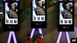 "Children use smartphones near monitors displaying a Chinese action movie ""Wolf Warrior 2"" at a cinema in Beijing, Aug. 10, 2017."