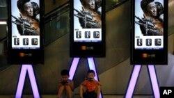 """资料照:中国儿童在北京一家影院张贴的""""战狼2""""电影广告下玩手机。(2017年8月10日)"""