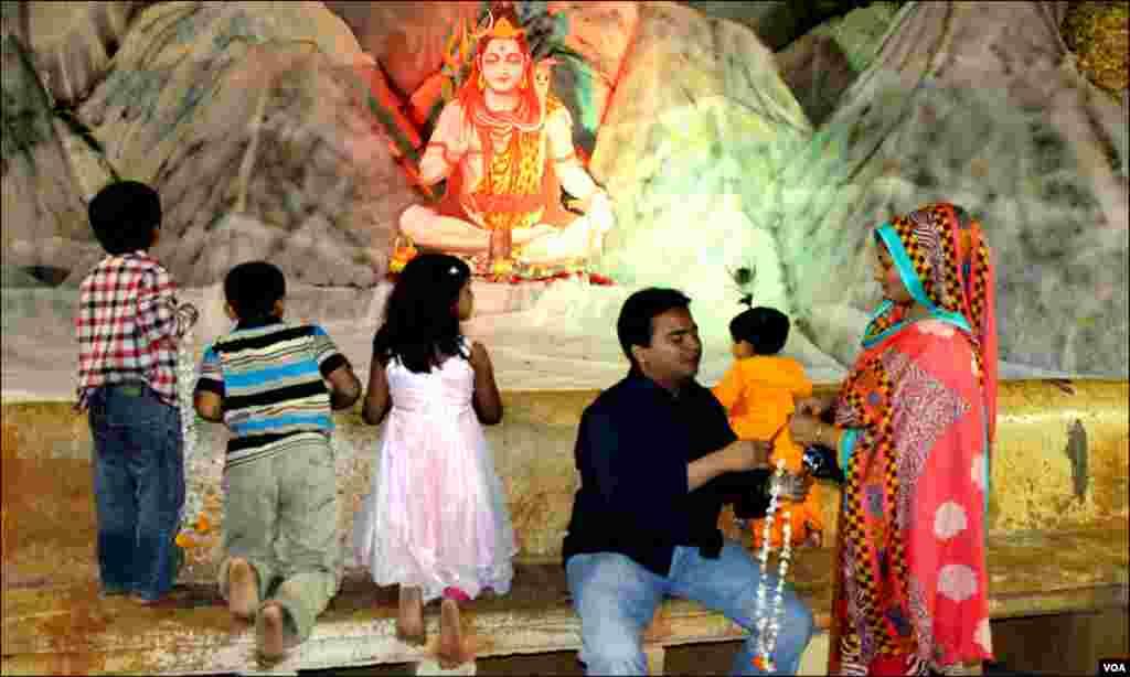 ہندو مذہبی عقیدت مند مذہبی تہوار کے موقع پر بھگوان کی مورتی پر پھول چڑھاتے اور پوجا کرتے ہیں