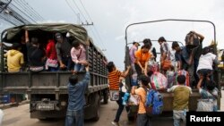 Cambodian workers ride on military trucks as they prepare to cross the Thai-Cambodia border.