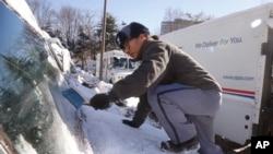 在首都华盛顿近郊马里兰州的贝塞斯达,美国邮政局邮递员丹尼•金爬上他的邮递车的前盖刮扫盖住车窗的冰雪。(2014年1月3日)