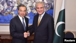 Pakistan's Foreign Minister Shah Mehmood Qureshi shakes hands with Chinese State Councilor and Foreign Minister Wang Yi at the Ministry of Foreign Affairs in Islamabad, Pakistan, Sept. 8, 2018. (Ministry of Foreign Affairs handout via Reuters).