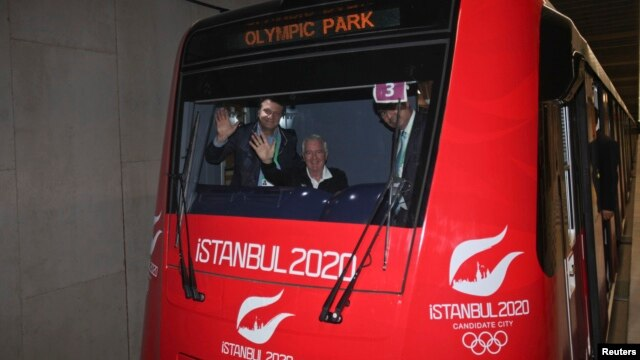 International Olympic Committee (IOC) Vice President and chairman of the IOC Evaluation Commission Craig Reedie (2nd L), and Hasan Arat, leader of the Istanbul 2020 Bid Committee (L), wave from a metro train in Istanbul March 24, 2013.