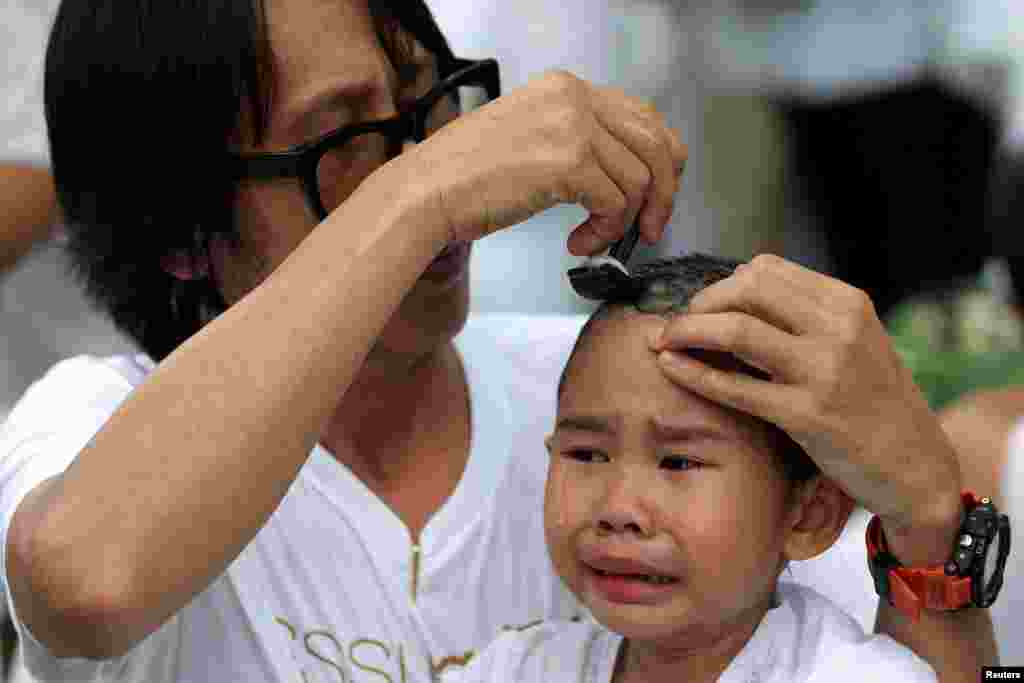 A devotee girl has her hair shaved by her father during a mass ceremony to mark the first anniversary of late Thailand's King Bhumibol Adulyadej's death, at the Sathira-Dhammasathan Buddhist meditation center in Bangkok.