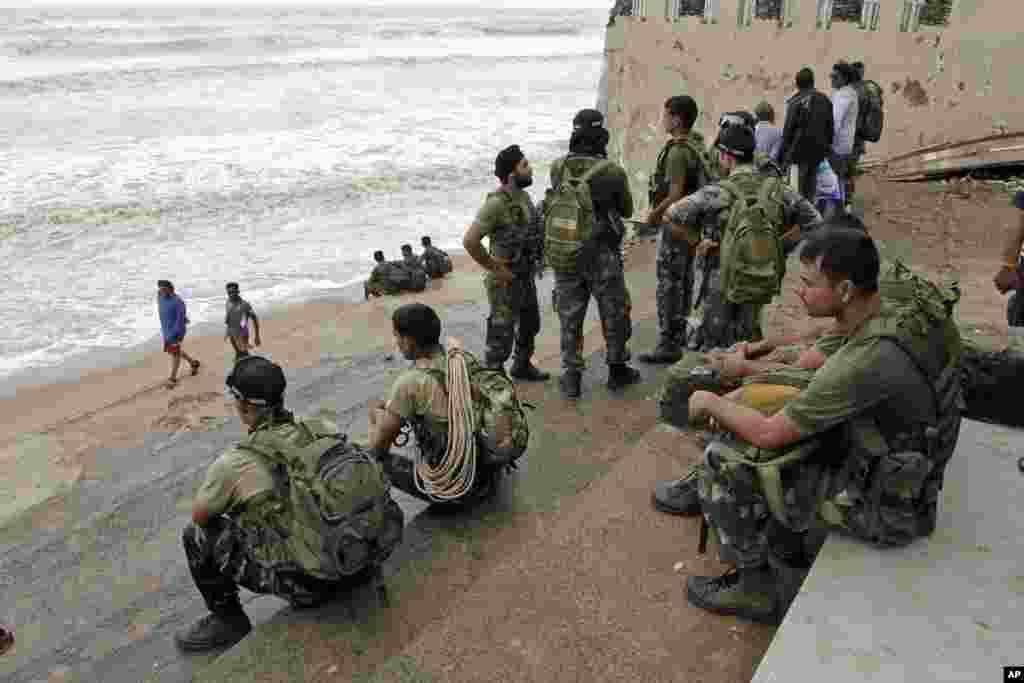 Para anggota Angkatan Udara India menunggu cuaca membaik di sebuah pantai menyusul datangnya Topan Phailin di Gopalpur, negara bagian Orissa di timur India (13/10). (AP/Bikas Das)