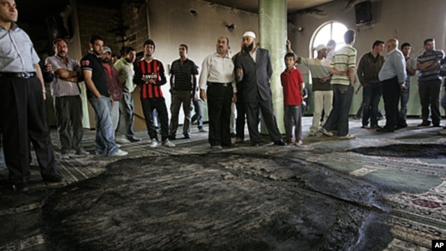 Palestinians inspect the damage following a fire inside a mosque in the West Bank village of al-Mughayyir, near Ramallah, June 7, 2011