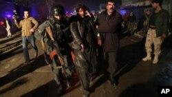 Fuerzas de seguridad afgana asisten a un herido tras la explosión.