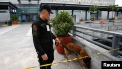 Cảnh sát và chó nghiệp vụ tại sân bay quốc tế Ninoy Aquino ở thành phố Pasay, Manila, ngày 1/9/2014.