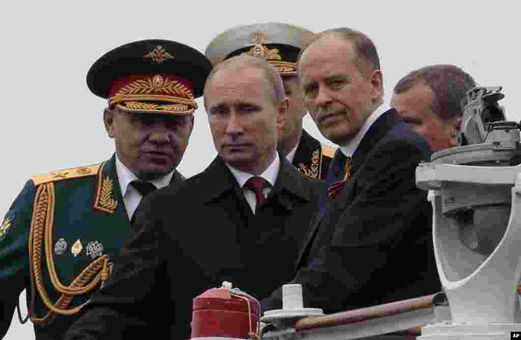 Russian President Vladimir Putin, flanked by Defense Minister Sergei Shoigu, left, and Federal Security Service Chief Alexander Bortnikov, right, arrives on a boat after inspecting battleships during a navy parade marking the Victory Day in Sevastopol, Crimea, May 9, 2104.