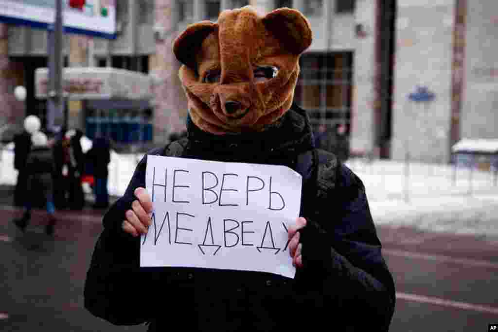 """A protester wearing a bear mask at the rally with a sign that reads """"Don't believe the bear"""" -- President Dmitri Medvedev's last name in Russian means bear, December 24, 2011. (VOA - Y. Weeks)"""