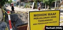 Warga melintas di lokasi proyek yang terhenti karena menjadi obyek OTT KPK. (Foto:VOA/Nurhadi)