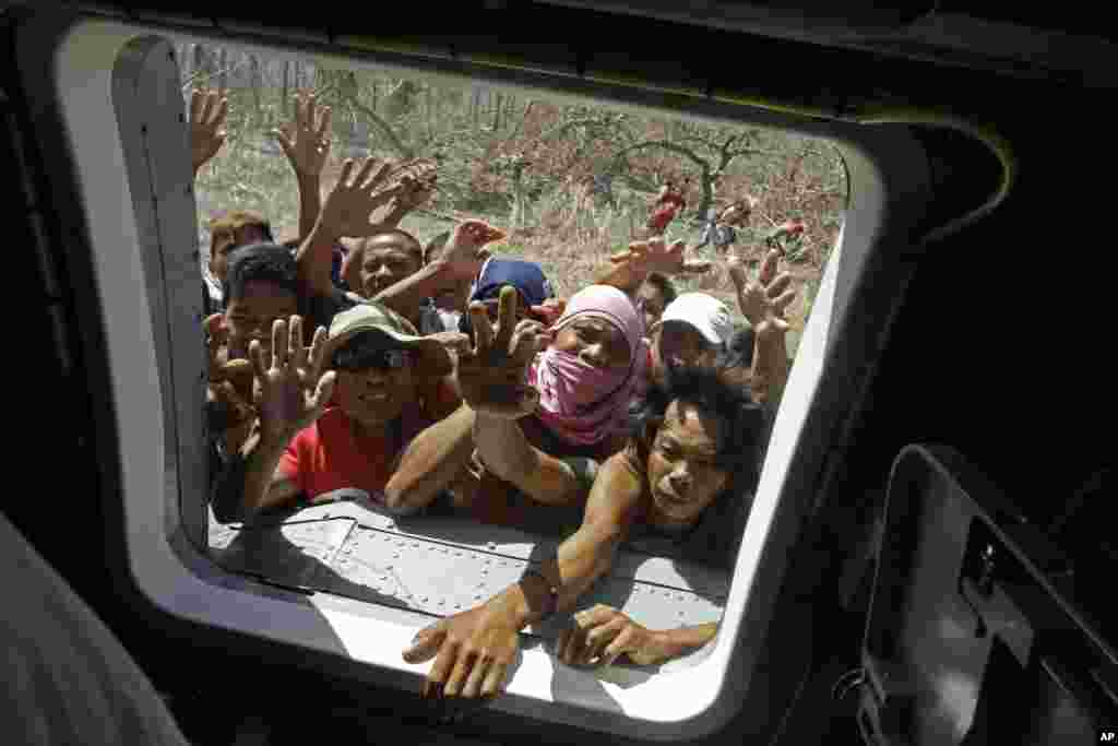 People rush to a window of a U.S. Navy Seahawk helicopter as crewmen deliver aid in an emergency drop in San Jose, Philippines, Nov. 18, 2013.
