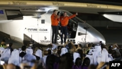 Bertrand Piccard (R) and Andre Borschberg (L), pilots of the solar powered Solar Impulse 2 aircraft, are greeted upon arrival at Al Batin Airport in Abu Dabi to complete its world tour flight on July 26, 2016, in the United Arab Emirates.